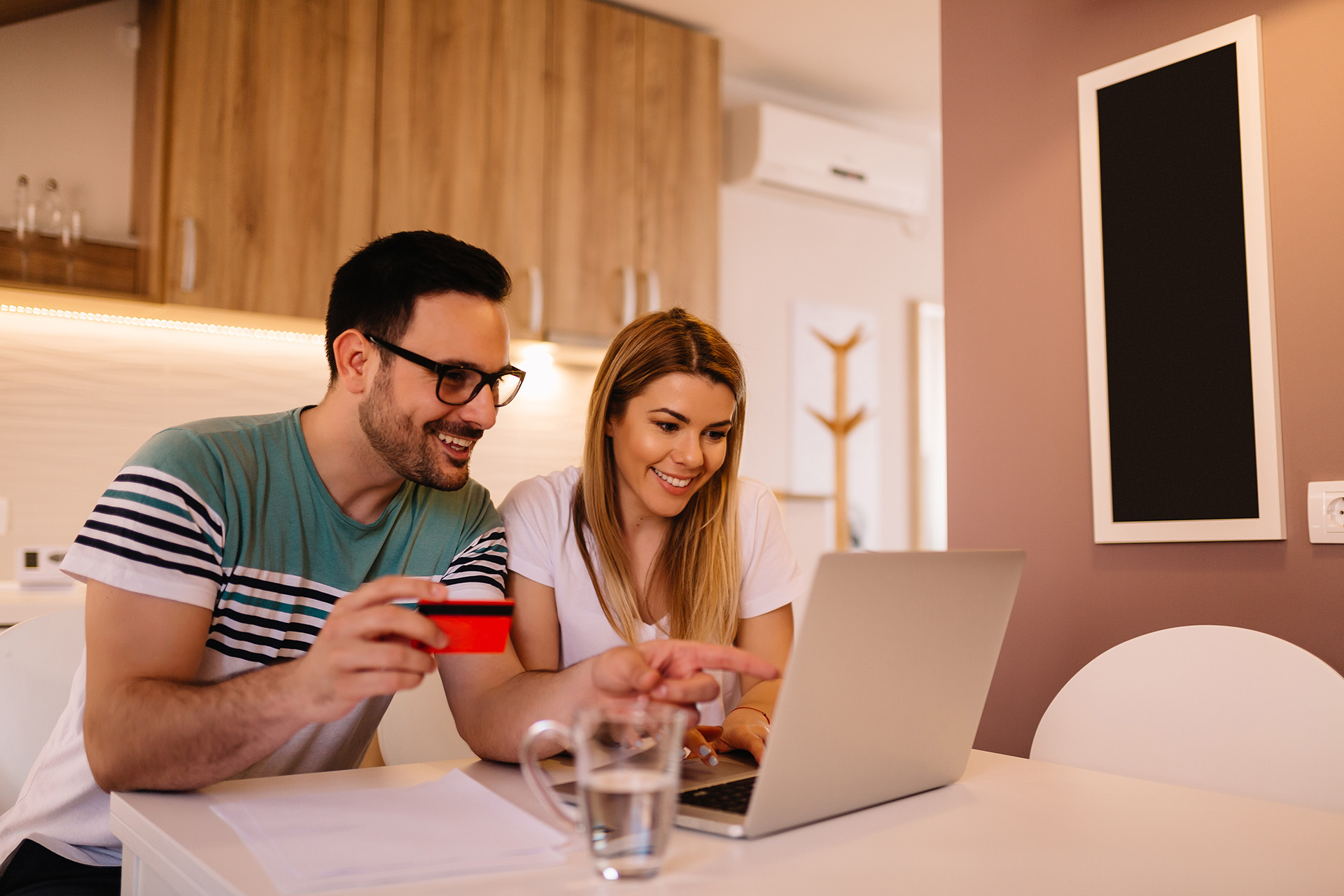 Portrait of young couple who is shopping online using credit card from their home